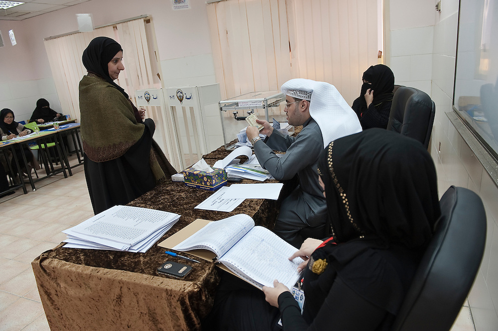 Elections officials checking the identification card of a Kuwaiti woman voter at a polling station in Kuwait City during the February 2 parliamentary elections. More than 400,000 Kuwaiti men and women are eligible to vote to choose from among some 285 candidates for a new 50-seat National Assembly (parliament).