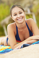 Happy Young Woman Relaxing on Beach