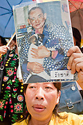 05 MAY 2010 - BANGKOK, THAILAND: A woman holds up a photo of Thai King Bhumibol Adulyade while she waits for his motorcade, Wednesday May 5. Wednesday was Coronation Day in Thailand, marking the 60th anniversary of the coronation of Thai King Bhumibol Adulyade, also known as Rama IX. He is the world's longest serving current head of state and the longest reigning monarch in Thai history. He has reigned since June 9, 1946 and his coronation was on May 5, 1950, after he finished his studies. The King is revered by the Thai people. Thousands lined the streets around the Grand Palace hoping to catch a glimpse of the King as his motorcade pulled into the palace. The King has been hospitalized since September 2009, making only infrequent trips out of the hospital for official functions, like today's ceremonies.   PHOTO BY JACK KURTZ