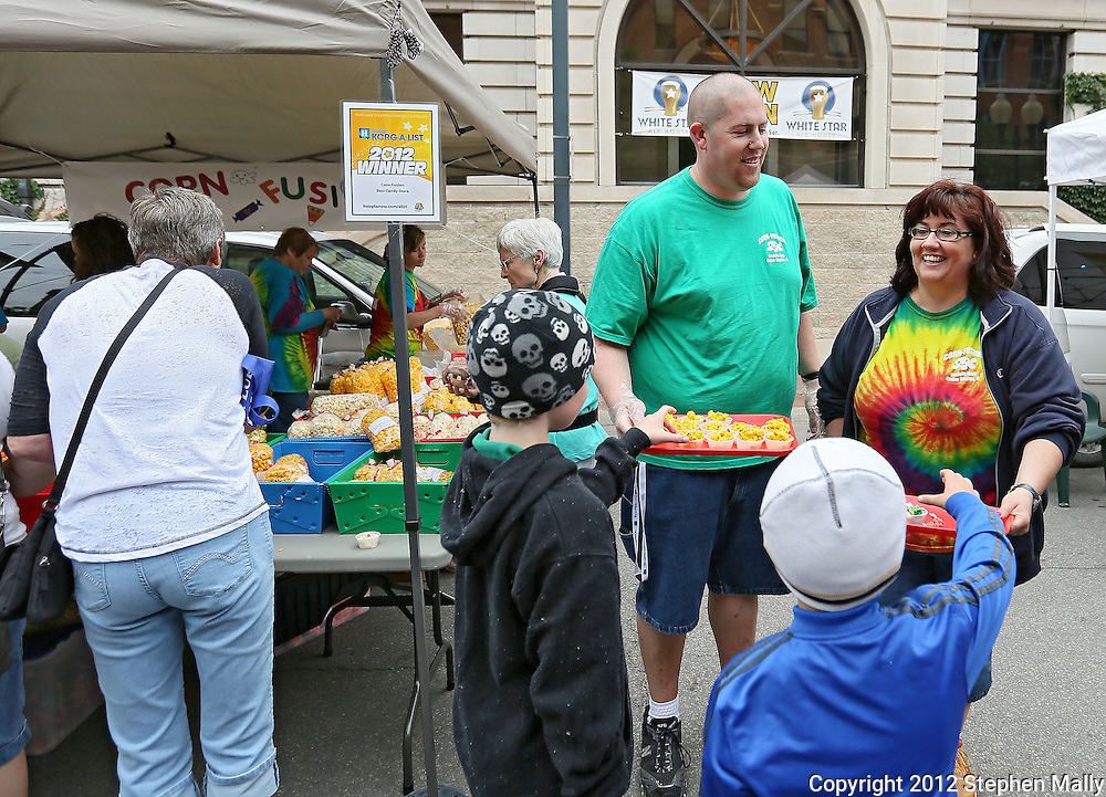 Ryan Fottral (from left) and Melissa Blanchett, of Corn-Fusion, hand out free samples of flavored popcorn at the Downtown Farmers' Market in Cedar Rapids on Saturday morning, June 2, 2012. There were 244 vendors who participated in the first market of the year. (Stephen Mally/Freelance)
