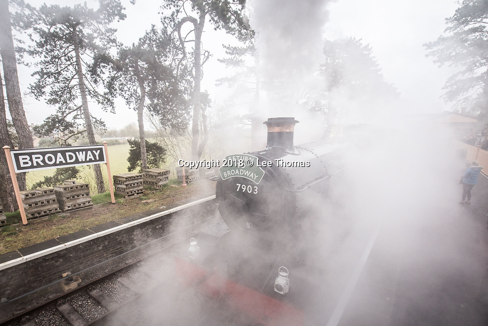 Broadway Station, Broadway, Worcestershire, UK. 30th March 2018.  A steam train carry members of the public departed from Broadway Station in the Cotswolds for the first time in almost 60 years today. On Good Friday, Lord Richard Faulkner of Worcester formally opened the station and traveled on the footplate of Great Western Railway-designed engine no.7903 'Foremarke Hall', the first public train to Cheltenham for 58 years. The new station has been built by GWSR volunteers to a similar design as the 1903 original station. Most of the stations on the former Stratford-upon-Avon to Cheltenham line were closed by British Railways in 1960 and the railway closed completely in 1976, with track and infrastructure removed by 1979. Pictured: Foremarke Hall departs the station engulfing the platform and onlookers. // Lee Thomas, Tel. 07784142973. Email: leepthomas@gmail.com  www.leept.co.uk (0000635435)