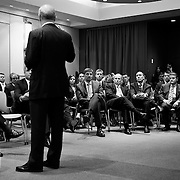 B&W Photo taken from behind a man speaking to a group of people seated auditorium style in a business presentation