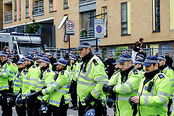 Britains tallest policeman, PC. Anthony Wallyn, forms part of a cordon as anti-fascists gather to protest against a march held by the English Defence League. Walthamstow London May 2015