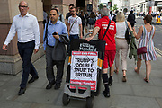 An Evening Standard newspaper vendor pulls his stand with yesterday's headline for the previous day's West End final edition, about US President Trump's controversial comments about Prime Minister Theresa May's handling of Brexit, and the leaked messages of British ambassador to Washington, Kim Darroch (who resigned the next day), in the City of London, the capital's financial district (aka the Square Mile), on 10th July 2019, in London England.