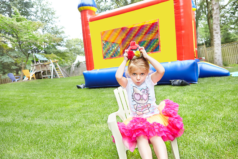 Lifestyle image of child sitting with a toy in front of a bouncy castle outside in her garden