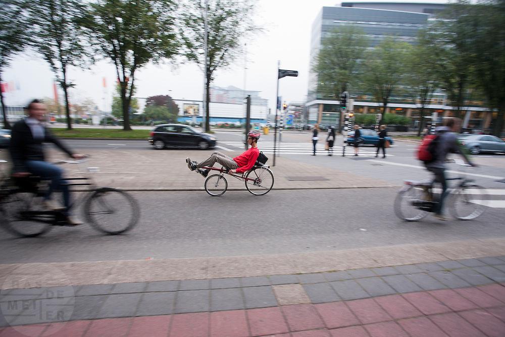 Een ligfietser rijdt bij de Jaarbeurs in Utrecht.<br /> <br /> A man on a recumbent bike is riding near the Jaarbeurs in Utrecht.