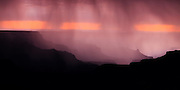 Rain from a monsoon thunderstorm falls into the Grand Canyon at sunset. Viewed from the North Rim.
