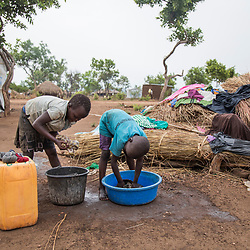 South Sudanese refugees Esta, 8 and Ludia, 6, from left, wash their clothes at the Bidi Bidi refugee settlement in north Uganda. They wash their clothes once a week using water that has to be carried in 20 kilogram containers from a nearby distribution point.