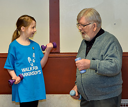 Pictured: Abby McConnell takes part in one of the exercises with Ronnie Downie from Burnside.<br /> <br /> A young fundraiser inspired by comedian Billy Connolly's battle with Parkinson's  prepares for a charity walk on April 15th - World Parkinson's Day - to raise funds for the charity. Abby McConnell (7) from Mount Florida met sufferers and took part in a seated exercise class specially designed for sufferers of the disease at Rutherglen West Parish Church in Glasgow.<br /> <br /> &copy; Dave Johnston / EEm