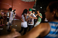 Residents in a dance class, in Complexo da Maré, Rio de Janeiro, Brazil, on Saturday, May 4, 1013...Complexo da Mare, is a complex of 16 communities, in the north zone of Rio de Janeiro. It is the largest complex of favelas with 130,000 residents. It is targeted for pacification as the city prepares for the 2014 World Cup and the 2016 Olympics. Four factions run the complex -  three drug gangs and the militia. The rival gangs fight for control of the drug trade. Although crime is low in the favelas by rule  of law enforced by the gangs, cross-fire shootings and gang violence is often high. Neighborhood associations are an integral part of community development within Mare, making up for a lack of government assistance. .