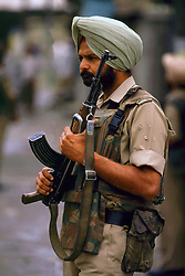 July 1997. Srinagar, Kashmir, India..An Indian soldier on foot patrol in the troubled region. The Indian government struggles to contain the rising insurgency amidst fears of a civil war in the region..Photo; Charlie Varley