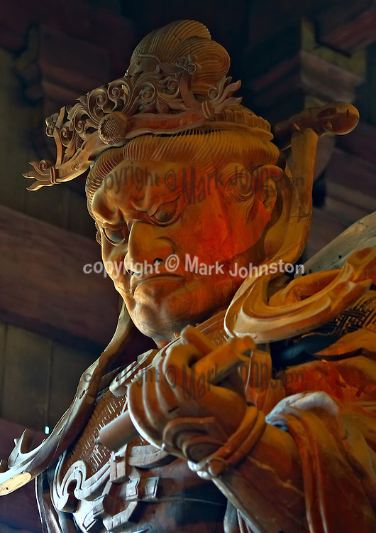 Inside the great hall of the Todaiji temple at Japan's ancient capital city of Nara are a number of guardian dieties that protect the environs.<br /> <br /> This one is Koumokuten [&quot;the wide-eyed guardian&quot;] who is positioned at the West.  His piercing eyes see through evil and he carries a writing brush and scroll.