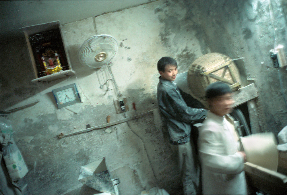 Workers in a small privately owned noodle making factory along the Yangtze river. There are many complaints that compensation does not reach the displaced people its meant to help due to corruption by local authorities. Chongqing, China. 2003