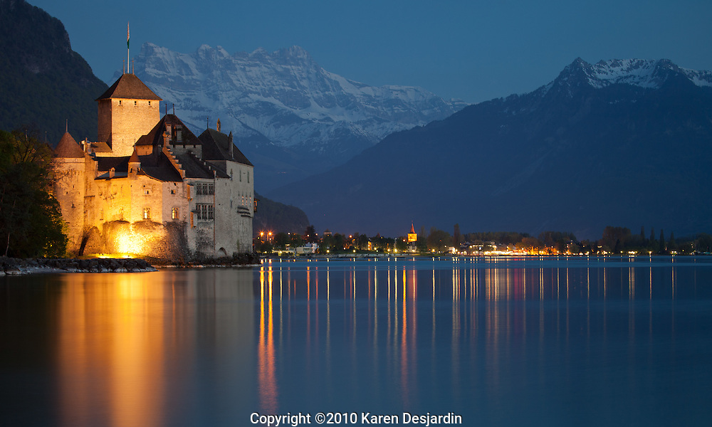 The Chateau du Chillon on Lake Geneva (Lac Léman), near the illuminated city of Villeneuve , Switzerland. The peaks of the Dents du Midi are visible in the background. The castle of Chillon was made popular by Lord Byron, who wrote the poem The Prisoner Of Chillon (1816) about François de Bonivard, a Genevois monk and politician who was imprisoned there from 1530 to 1536; Byron also carved his name on a pillar of the dungeon. The castle is one of the settings in Henry James's novella Daisy Miller (1878). http://www.gettyimages.com/detail/photo/chateau-chillon-switzerland-illuminated-at-high-res-stock-photography/470803979