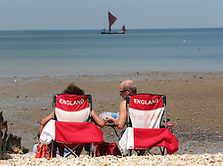 Image licensed to i-Images Picture Agency. 21/06/2014. Whitstable, United Kingdom. Two England fans take to the beach to enjoy the hot weather at Whitstable in Kent.  Picture by Stephen Lock / i-Images