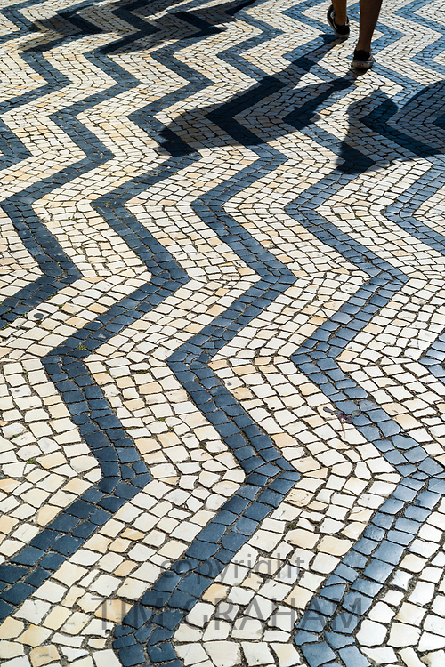 Walker and geometric tiles form shapes and patterns of wavy lines on paving tiles in Aveiro, Portugal