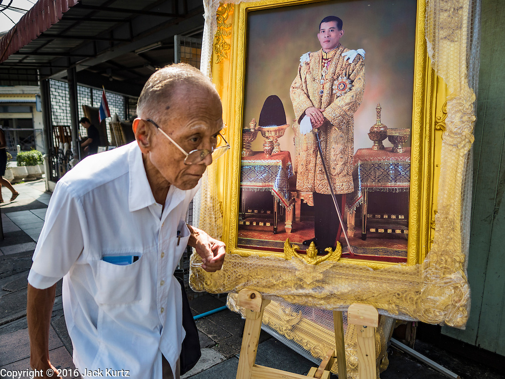 01 DECEMBER 2016 - BANGKOK, THAILAND:  A man walks past a portrait of HRH Crown Prince Maha Vajiralongkorn, who will soon be the new King of Thailand. Thailand's parliamentary body, the National Legislative Assembly, invited HRH Crown Prince Maha Vajiralongkorn to be king following the death of the Crown Prince's father, Bhumibol Adulyadej, the Late King of Thailand. The invitation marked the formal beginning of the process of naming the new King, although Crown Prince Vajiralongkorn was the heir apparent and Bhumibol's appointed successor. Shops that sell royal paraphernalia are now selling new portraits of  Crown Prince Vajiralongkorn which will be displayed alongside portraits of his late father. King Bhumipol died on Oct 13.     PHOTO BY JACK KURTZ