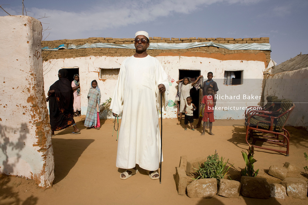 """Mr Matar Mohammed, a former farmer from Taweela, a Darfur village in the 4 sq km Abu Shouk refugee camp, (disputedly) home to 38,000 displaced persons, on the outskirts of Al Fashir. Mr Mohammed was once a successful farmer who grew tobacco and sorghum and has occupied this house with his 14 family members since May 2004, surviving on twice a day aid hand-outs. Many family members and friends have been killed . """" We had a good life,"""" he says adding """"we would go back if security was guaranteed .."""""""
