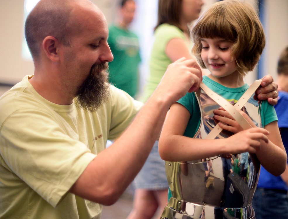 (20110611, Moline, Illinois)..Chris LaRoche of East Moline helps his daughter Raimi, 7, put on a suit of plate armor following a presentation by Randy Cieszynski, or Sir Randall, to show off medieval armor to kids aged 5 and up at the Moline Library in Moline, Illinois on Saturday, June 11, 2011...Brooks Canaday, Moline Dispatch.