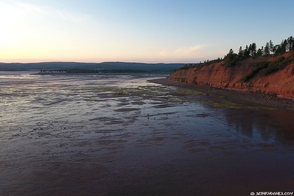 People exploring the beach at low tide in the Bay of Fundy, Five Islands Provincial Park, Nova Scotia Canada.