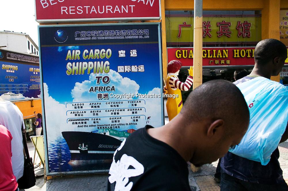 GUANGZHOU, 3. Mai , 2010:.eine Afrikaner geht  vor einem Werbeschild fuer  .Frachttransporte nach Afrika  vorbei...