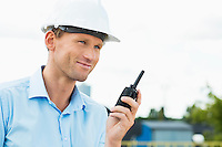 Smiling architect holding walkie-talkie at construction site