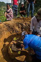 An Ixil woman looks on as FAFG staff and IFIFT students take measurements while exhuming the remains of an Ixil man killed by government security forces. After digging to locate the remains and the first positive  discovery is made a more careful approach is taken and anthropolgists begin the refined process of removing the final blanket of soil.