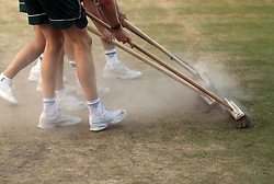 Ground staff sweep the baseline on court four on day seven of the Wimbledon Championships at The All England Lawn Tennis and Croquet Club, Wimbledon.