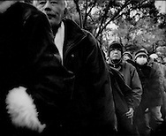 Homeless men line up for a meal at a temporary tent village set up by a Japanese NPO (non-profit organization), Hibiya Park, Tokyo, Japan.