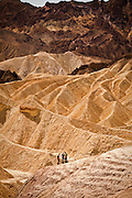 Tourists at the badlands at Zabriskie Point looking toward Golden Canyon in Death Valley National Park, Nevada, USA. Zabriskie point was once the home of twenty-mule team borax mines.