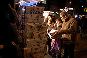 Visitors to Theatreland in London's West End, read newspapers at a kiosk lit by spotlights on Tottenham Court Road.