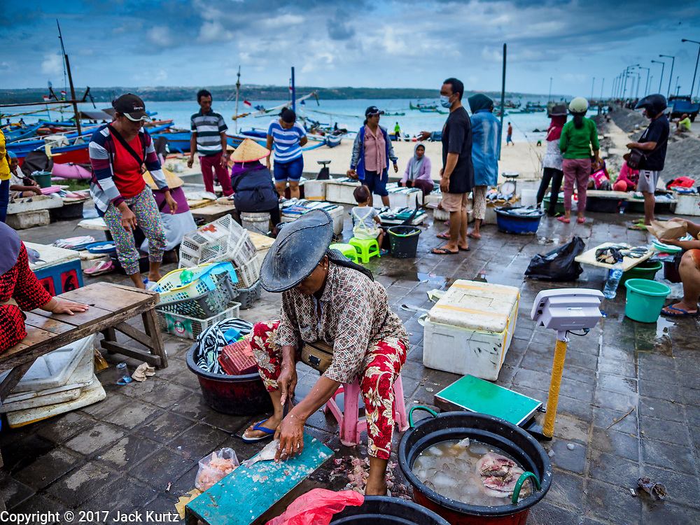 03 AUGUST 2017 - KUTA, BALI, INDONESIA: An informal fish market on the jetty next to Jimbrana Beach in Kuta. The beach is close to the airport and a short drive from other beaches in southeast Bali. Jimbrana was originally a fishing village with a busy local market. About 25 years ago, developers started building restaurants and hotels along the beach and land prices are rising. The new emphasis on tourism is changing the nature of the area but the fishermen are still busy very early in the morning.     PHOTO BY JACK KURTZ