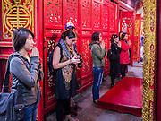 31 MARCH 2012 - HANOI, VIETNAM:   A western tourist looks at her digital camera while Vietnamese pray in Ngoc Son Temple, which was reportedly built during the Tran Dynasty (ca 1225) in the Old Quarter of Hanoi, Vietnam. The temple is dedicated to Tran Hung Dao, a Vietnamese national hero who defeated an invading Mongol army in the 13th century.      PHOTO BY JACK KURTZ