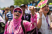 "09 MAY 2014 - BANGKOK, THAILAND: Thai anti-government protestors cheer for Suthep Thaugsuban as he walks past Government House in Bangkok. Thousands of Thai anti-government protestors took to the streets of Bangkok Friday to start their ""final push"" to bring the popularly elected of government of Yingluck Shinawatra. Yingluck has already been forced out by a recent court ruling that forced her to resign and she is facing indictment by the National Anti Corruption Commission of Thailand for alleged improprieties related to a government rice price support scheme. The protestors Friday were marching to demand that she not be allowed to return to politics. The courts have not banned her party, Pheu Thai, which has formed an interim caretaker government to govern until elections expected in July, 2014. Suthep Thaugsuban, secretary-general of the People's Democratic Reform Committee (PDRC),  said the president of the Supreme Court and the new senate speaker, who would be selected Friday, should set up an ""interim people's government and legislative assembly."" He went onto say that if they didn't, he would.     PHOTO BY JACK KURTZ"