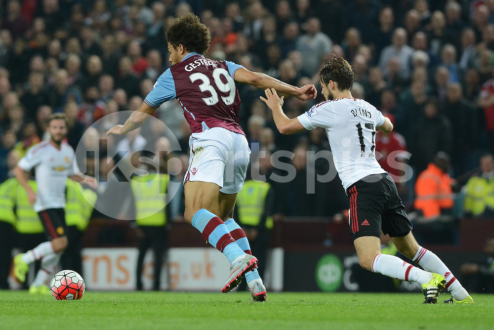 Aston Villa's Rudy Gestede holds the ball up watched by Manchester United's Daley Blind during the Barclays Premier League match between Aston Villa and Manchester United at Villa Park, Birmingham, England on 14 August 2015. Photo by Garry Griffiths.