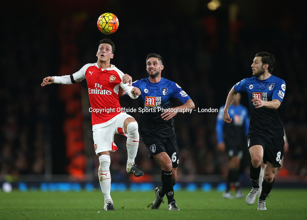 28 December 2015 - Premier League - Arsenal v AFC Bournemouth :<br /> Mesut Ozil holds off a challenge from Andrew Surman, with Dan Gosling (4) covering for Bournemouth.<br /> Photo: Mark Leech