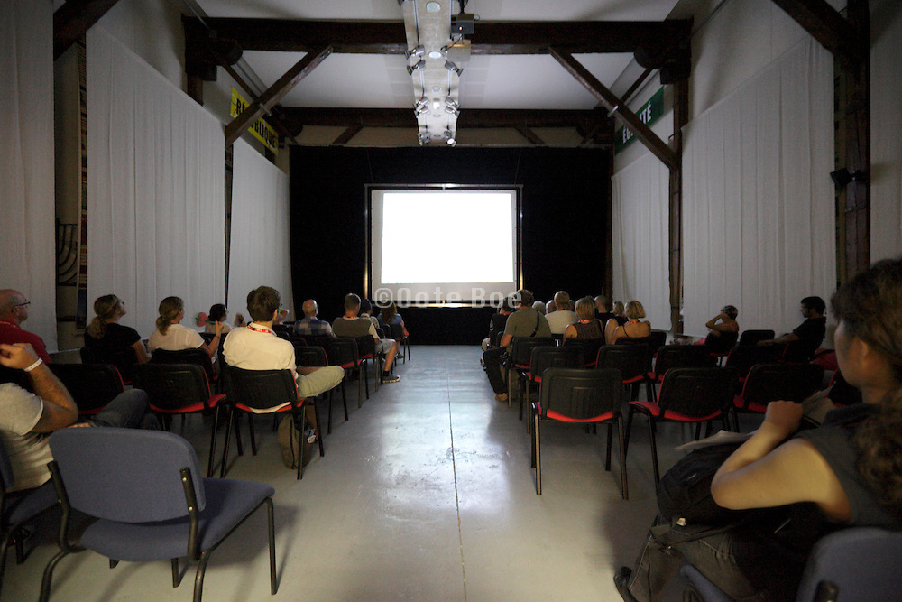 people facing a blank projection screen