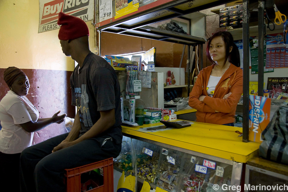 A local man keeps guard as a Chinese woman tends the till in a mini supermarket in the shanty town of Zhakele, near the platinum mines of Phokeng and Rustenburg, North West province, South Africa, April 30, 2008. Photo Greg Marinovich