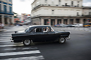 A passenger looks out the window of an old American car used as a taxi in Havana, Cuba