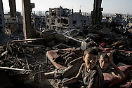 Gaza Strip, Gaza City: Palestinian kids lay on a mattress in their destroyed by strikes house in Al Shaaf neighbourhood during a 72 hours ceasefire on August 11, 2012. ALESSIO ROMENZI