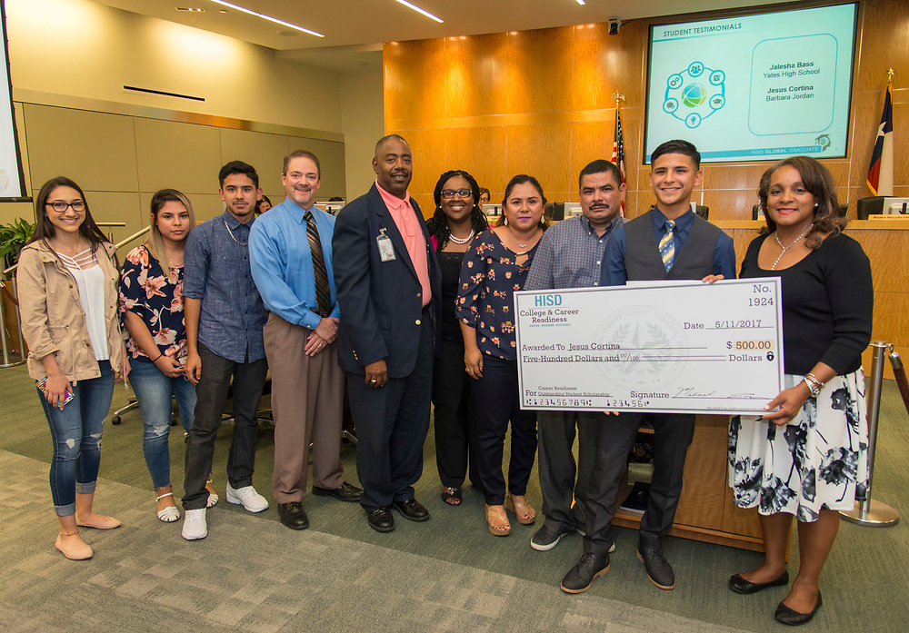 Houston ISD Trustee Rhonda Skillern-Jones poses for a photograph with College and Career Readiness scholarship recipient Jesus Cortina and his family during a Houston ISD Board of Trustee meeting, May 11, 2017.
