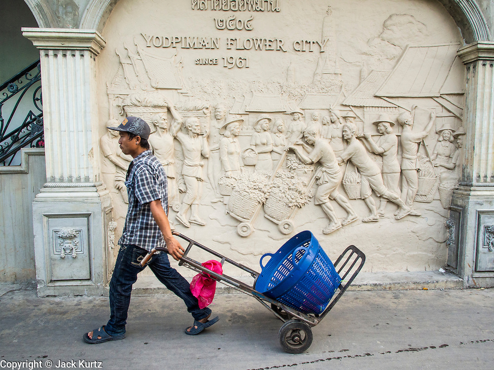 01 APRIL 2014 - BANGKOK, THAILAND:   A porter hauls an empty basket past the entrance to the flower market in Bangkok. The Yodpiman Flower Market (also called Pak Khlong Talat) is being renovated and gentrified. The market opened in 1961 and has been a Bangkok landmark for more than 50 years, is being turned into a high end mall. Many of the flower and vegetable vendors in the market may be forced out.    PHOTO BY JACK KURTZ