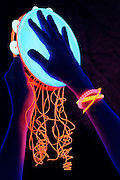 A pair of hands playing a glowing tambourine with colorful ribbons in a dark environment.Black light