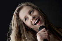 Young woman singing into microphone close-up