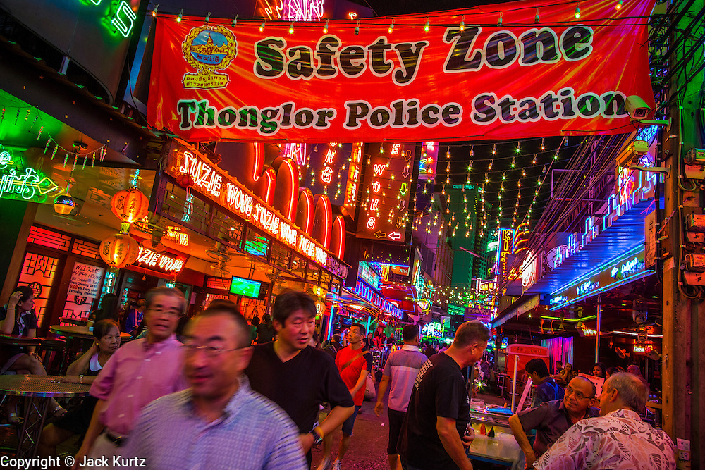 "12 JANUARY 2013 - BANGKOK, THAILAND:  Tourists wander through the Soi Cowboy red light district in Bangkok. Prostitution in Thailand is illegal, although in practice it is tolerated and partly regulated. Prostitution is practiced openly throughout the country. The number of prostitutes is difficult to determine, estimates vary widely. Since the Vietnam War, Thailand has gained international notoriety among travelers from many countries as a sex tourism destination. One estimate published in 2003 placed the trade at US$ 4.3 billion per year or about three percent of the Thai economy. It has been suggested that at least 10% of tourist dollars may be spent on the sex trade. According to a 2001 report by the World Health Organisation: ""There are between 150,000 and 200,000 sex workers (in Thailand).""    PHOTO BY JACK KURTZ"