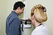 Female doctor weighing male patient in an examination room of a medical office, Tucson, Arizona..Media Usage:.Subject photograph(s) are copyrighted Edward McCain. All rights are reserved except those specifically granted by McCain Photography in writing...McCain Photography.211 S 4th Avenue.Tucson, AZ 85701-2103.(520) 623-1998.mobile: (520) 990-0999.fax: (520) 623-1190.http://www.mccainphoto.com.edward@mccainphoto.com
