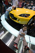 Seoul Motor Show 2005 at Korea International Exhibition Center (KINTEX). The big international players are exhibiting alongside local auto makers and their cars are a big hit with Koreans, here kids are having fun with a Honda S2000 cabriolet.
