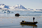 Eco-tourists explore the Kings Fjord (Kongsfjorden) in western Spitsbergen (Svalbard) with zodiacs.