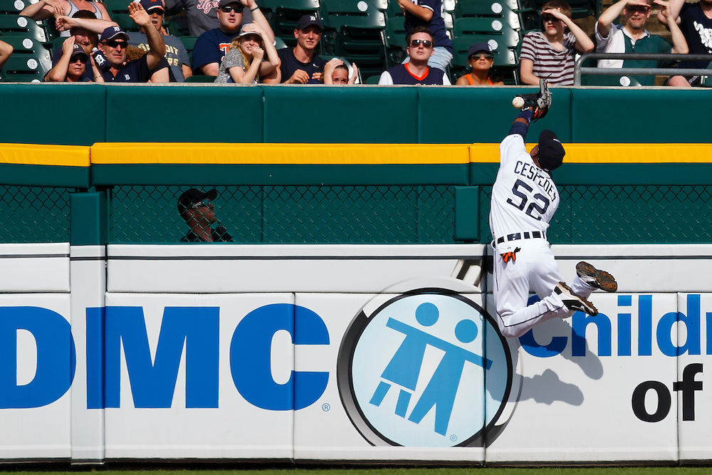 Jun 14, 2015; Detroit, MI, USA; Detroit Tigers left fielder Yoenis Cespedes (52) leaps onto the left field wall in an attempt to catch a ball hit by Cleveland Indians right fielder Brandon Moss (not pictured) for a home run in the ninth inning at Comerica Park. Detroit won 8-1. Mandatory Credit: Rick Osentoski-USA TODAY Sports