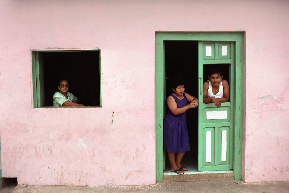Family looking out the front door and window of their pink house, Lerma Village, Yucatan, Mexico.